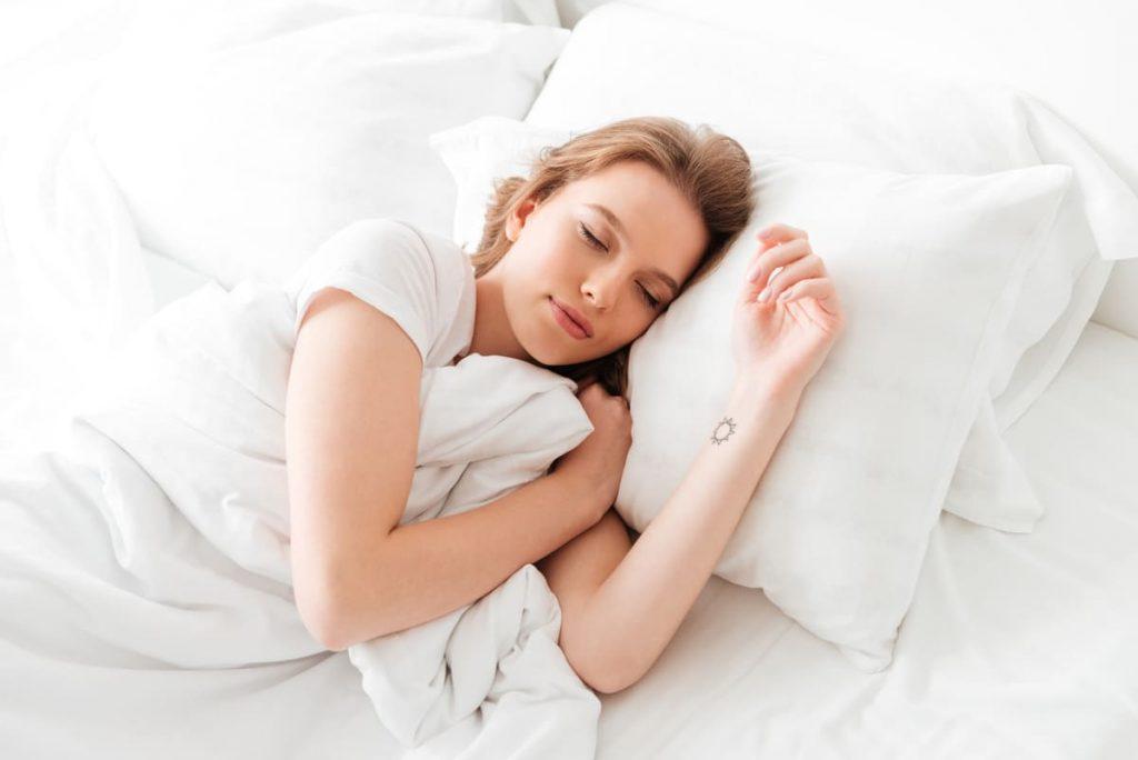 femme dormant sur un oreiller cervical